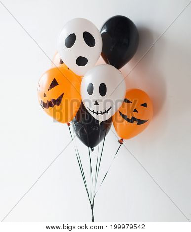 holidays, decoration and party concept - bunch of scary air balloons for halloween over white background