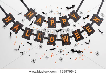 holidays, decoration and party concept - happy halloween festive paper black garland or banner over white background