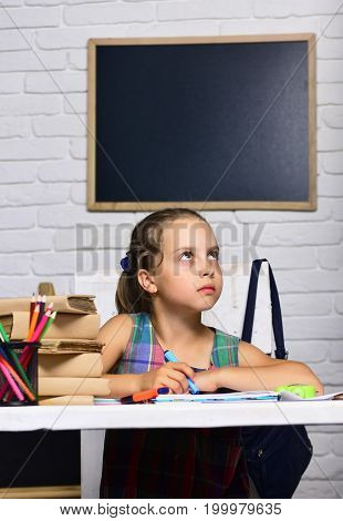 Schoolgirl With Thoughtful Face Draws In Art Book