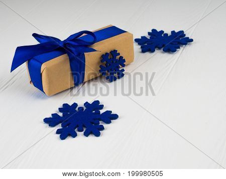 New Christmas Gift With Blue Ribbon, Bowknot, Next Blue Snowflakes. On White Wood Background, Copy S
