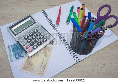 Stock market table analysis calculator and pen indicates research and analysis with cash. Money and a calculator