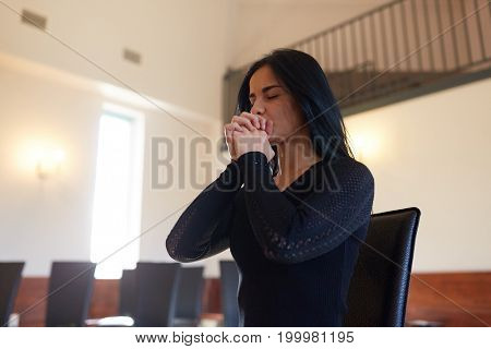 burial, people and mourning concept - unhappy woman praying god at funeral in church