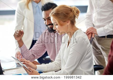 business, startup and people concept - international creative team with tablet pc computer in office