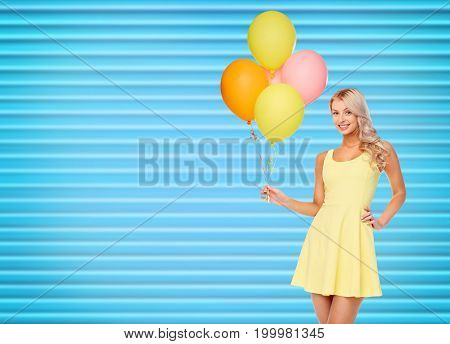 people, holidays and summer party concept - happy young woman or teen girl in yellow dress with helium air balloons over ribbed blue background