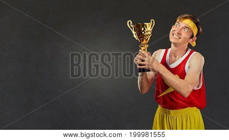 A thin, thin, thin guy with a champion's cup in his hands. Comedy humor in a sports champion.