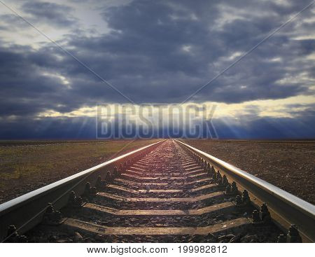 rails going away into the gloomy distance. rails going away into the dark sky landscape