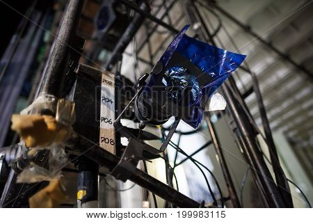 hardware, perfomance, backstage concept. there is important technical equipment of theater's backstage like spotlight with blue filter for creating dreamy and mysterious atmosphere