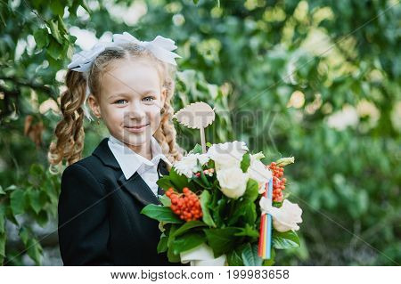 Portrait of a beautiful young first-grader with bouquet in a school uniform on the background autumn park. Farewell Bell. day of knowledge. beginning of the school year.