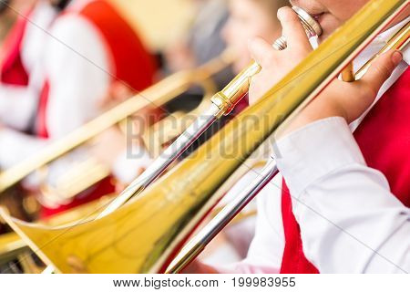 musical instrument, brass band and celebration concept - closeup playing trombone with mouthpiece and male hands, holiday performance of musicians in red and white concert suits, selective focus