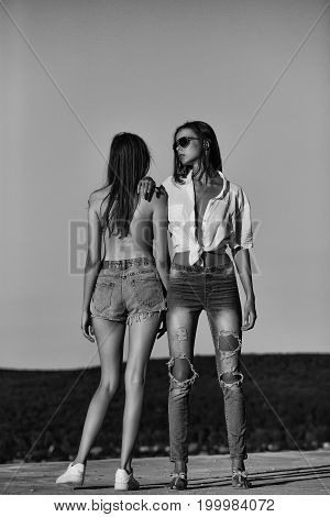 girls or women in jeans and shorts topless in sunglasses outdoor on sunny day standing on blue sky background