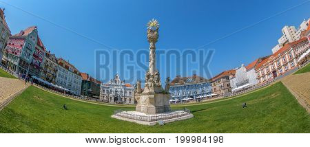 TIMISOARA ROMANIA - AUGUST 16 2017: Panoramic view of one part at Union Square in Timisoara Romania with old buildings. Trinity Statue and serbian vicariate in foreground.