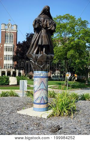 JOLIET, ILLINOIS / UNITED STATES - JULY 17, 2017: A sculpture of Mother Mary Alfred Moes, O.S.F., assisting a child, stands on a mosaic pedestral, in a traffic island, in front of the University of Saint Francis.