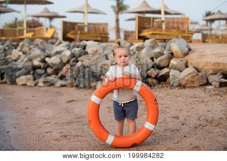 Boy child with cute serious face blond long hair wearing white shirt and blue shorts standing and holding orange life ring saver at sand beach on background of stones sunbeds and sun parasols