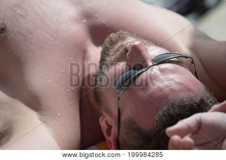 Young man in black sunglasses with bare athletic chest. Relaxation and summer vacation concept. Man relaxing with hands clasped behind head. Boy with bearded face having sunbathing.