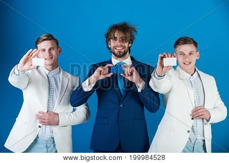 Happy men wearing formal suits. Information and cooperation. Business ethics concept. Businessmen showing blank cards. Group of people posing on blue background.