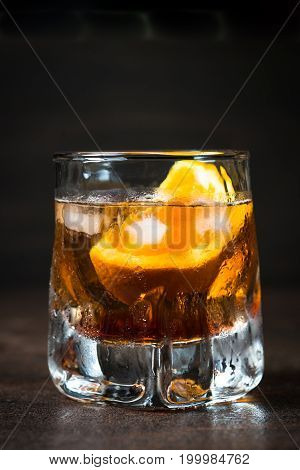 Negroni cocktail in glass on dark. Strong alcohol drink.