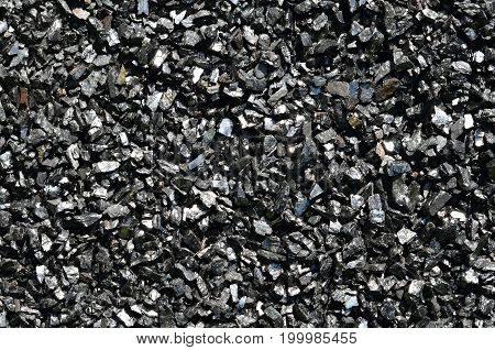 Background of charcoal anthracite fines in the sun.
