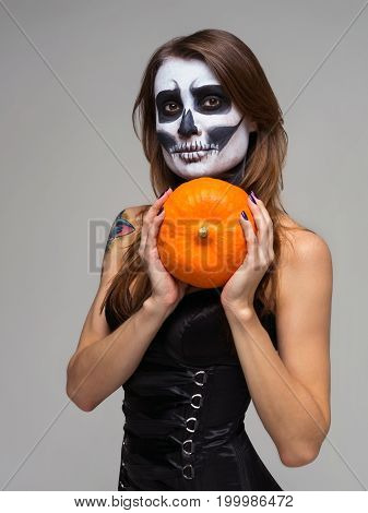 Portrait of woman with halloween skeleton makeup holding pumpkin over gray background.