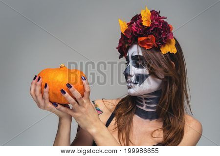 Portrait of young beautiful girl with fearful halloween skeleton makeup with a wreath Katrina Calavera made of flowers on her head, holding pumpkin over gray  background.