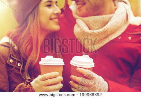 love, drinks and people concept - close up of happy young couple with coffee cups in autumn park