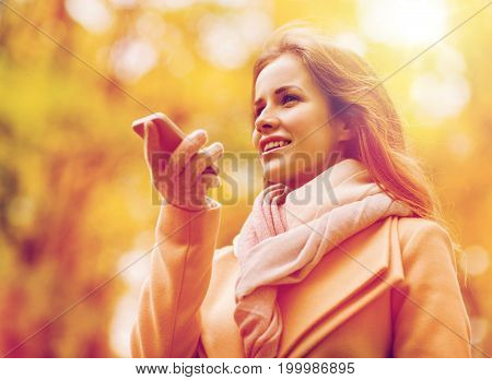 season, technology and people concept - beautiful young woman in autumn park and using voice command recorder on smartphone