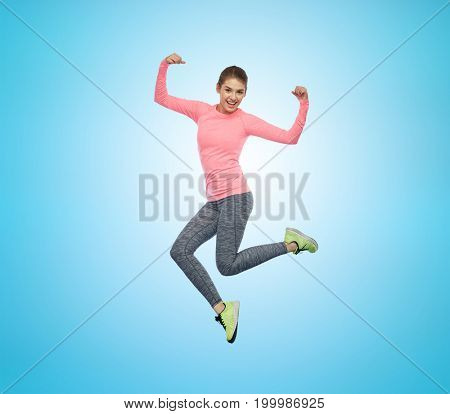 sport, fitness, motion and people concept - happy smiling young woman jumping in air and showing power gesture over blue background