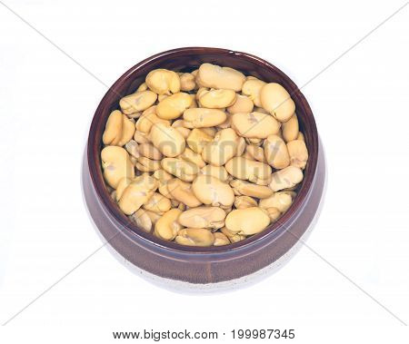 Organic dry broad haba beans in ceramic bowl isolated on white background
