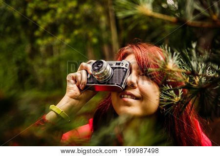 Picture of girl with camera in woods at summer afternoon