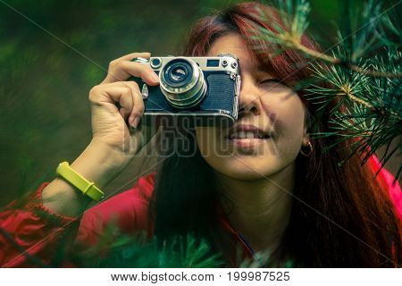 Brunette in red jacket takes pictures in park during day