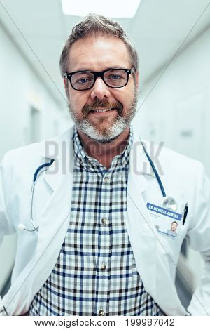 Portrait of happy and relaxed doctor standing in hospital. Man in lab coat in clinic looking at camera.