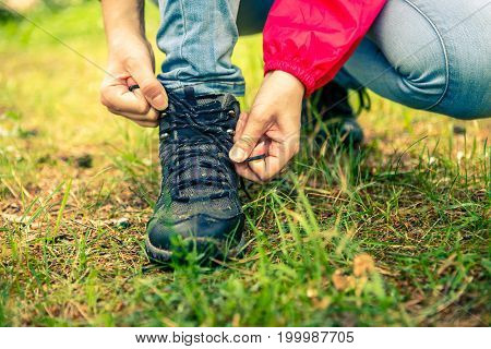 Image of woman tying shoelaces to shoes in woods by day