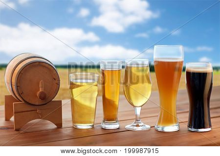 brewery, drinks and alcohol concept - different types of beer in glasses and barrel on table over cereal field and blue sky background