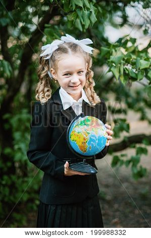 Portrait of a beautiful young first-grader holding the globe with russian text in a festive school uniform on the background park. Farewell Bell. day of knowledge. beginning of the school year.