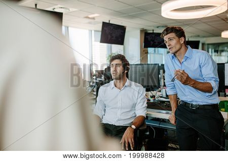 Business manager explaining new ideas to colleagues during a meeting in office. Corporate professionals having meeting in office.
