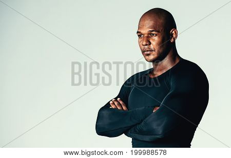 Portrait of muscular men in long sleeve gym t-shirt. Male model wearing bodybuilding gym training compression tights t-shirt over grey background.