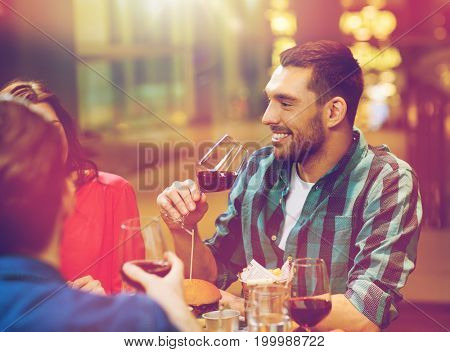 leisure, eating, food and drinks, people and holidays concept - smiling friends having dinner and drinking red wine at restaurant