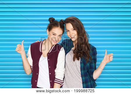 people, teens and friendship concept - happy smiling pretty teenage girls or friends hugging and showing thumbs up over blue ribbed background