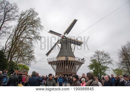 Keukenhof, Netherlands - April 21, 2017: Old windmill with many people in famous garden in Keukenhof.