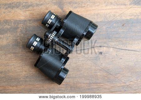 Old prism black color binoculars on vintage wooden background top view closeup