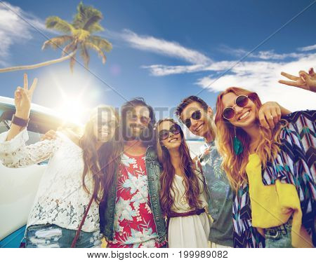 summer holidays, road trip, travel and people concept - smiling young hippie friends at minivan car showing peace hand sign over beach background