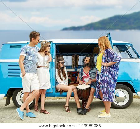 summer holidays, road trip, travel and people concept - happy young hippie friends with tom-tom drum playing music at minivan car over beach background