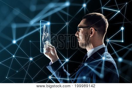 business, augmented reality and future technology concept - businessman in glasses working with transparent tablet pc computer and virtual low poly shape projection over black background