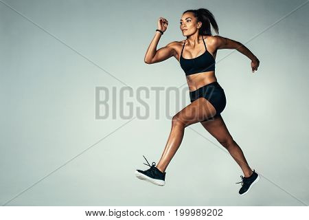 Full length shot of fitness woman running over grey background. Hispanic female model doing running exercise.