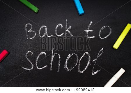 Back To School Message On Blackboard Inscribed With Colorful Chalk For Background.
