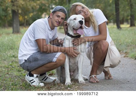 The young couple in love relaxes in nature with their dog - Dogo Argentino. They enjoy together on a beautiful and sunny summer day