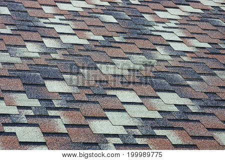 Colored texture of a fragment of roofing tiles on the roof of the house