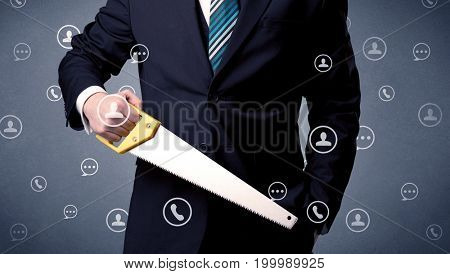 Thoughtful businesman holding tool with communication symbols around