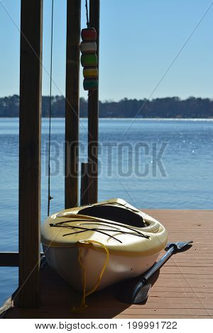 single yellow canoe with paddle resting on a boat dock