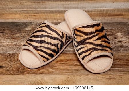 Slippers with tiger pattern on old wooden floor