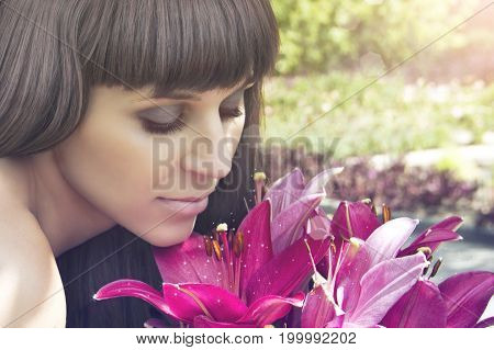 Beautiful girl looks at flowers and inhales their fragrance close-up